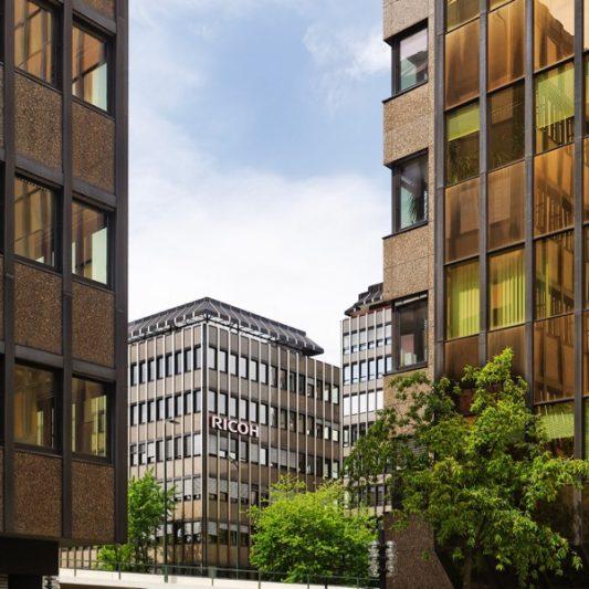 Bürocenter Nord Ausschnitt Fassade Blick zwischen zwei Gebäuden auf gegenüberliegende Bürogebäude rötliche Granitfassade Scheiben teils kupferfarben