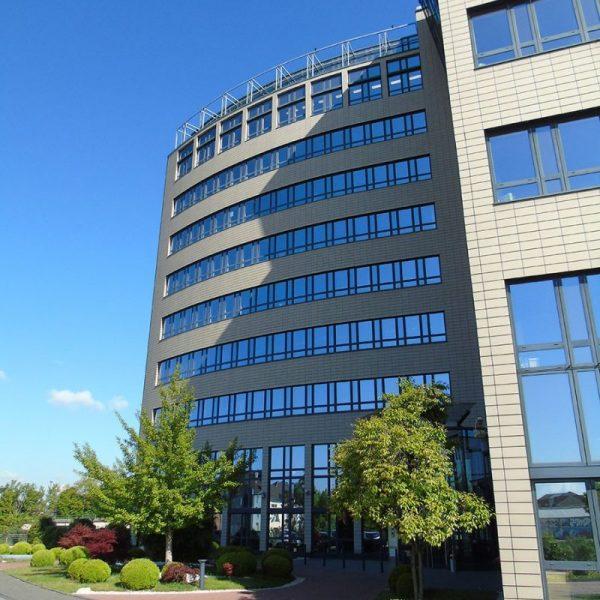 Arcadia Parc Fassadendetail Blick auf Rundgebäude mit Bepflanzung davor