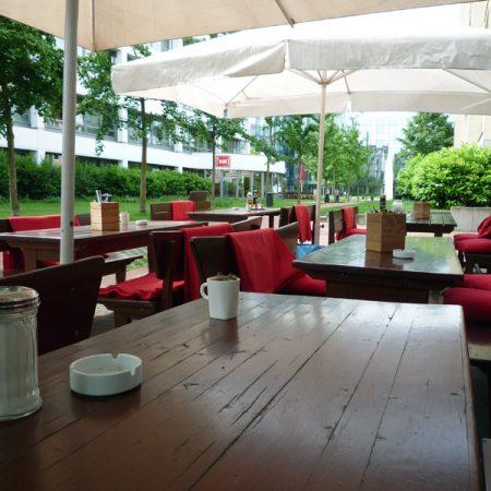 Prinzenpark Außenansicht Terrasse Gastronomie mit weißen Sonnenschirmen roten Sitzkissen Decken