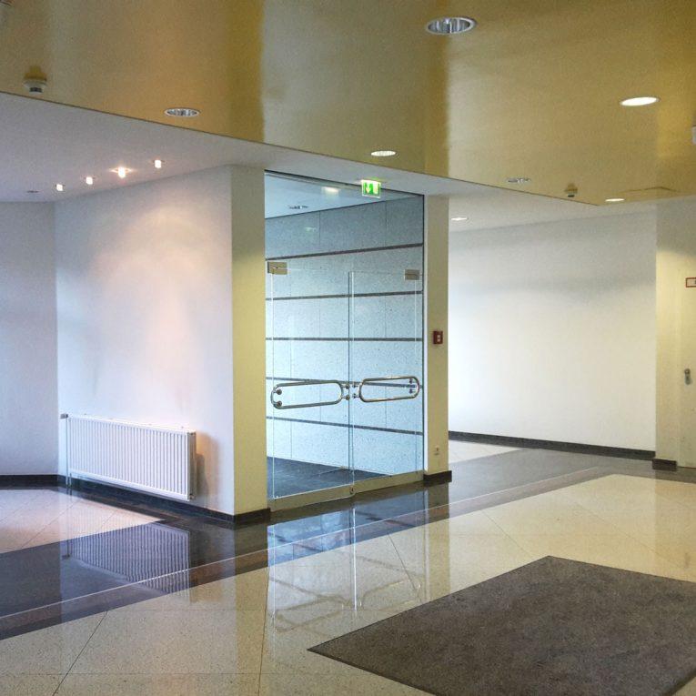 Bürocenter Nord Nebengebäude Innenansicht Entrée mit Granitboden und Glastüre