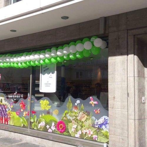 Am Wehrhahn Außenansicht Detail Schaufenster Ladenlokal dm geschmückt mit grünen und weißen Luftballons