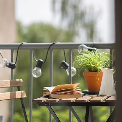Small wooden table with chairs on nicely decorated balcony