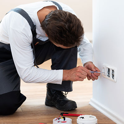 Electrician in grey overalls is screwing on sockets