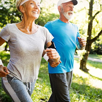 Pensioner couple jogging happily through Aaper Forest in Düsseldorf Rath