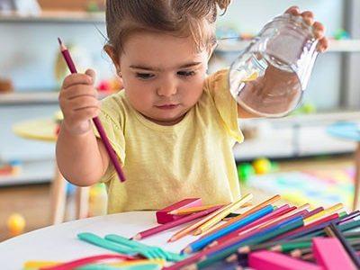 Kleines Mädchen mit bunten Stiften in der Kindertagesstätte der Arcadia Höfe
