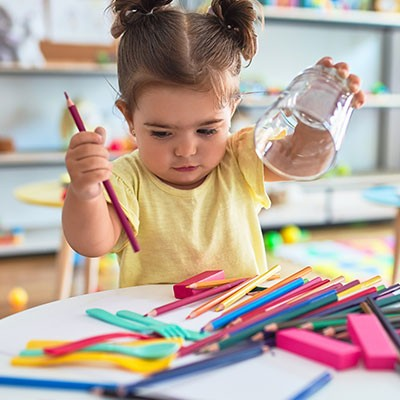 Little girl playing with colored pencils in kindergarten