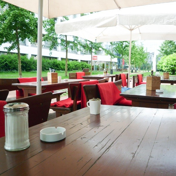 Prinzenpark terrace gastronomy with white sunshades and red woolen blankets on wooden benches