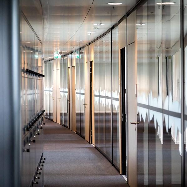 Triangulum Innenansicht Detail gerundeter Flur mit Spinten links und Büroeingangstüren rechts