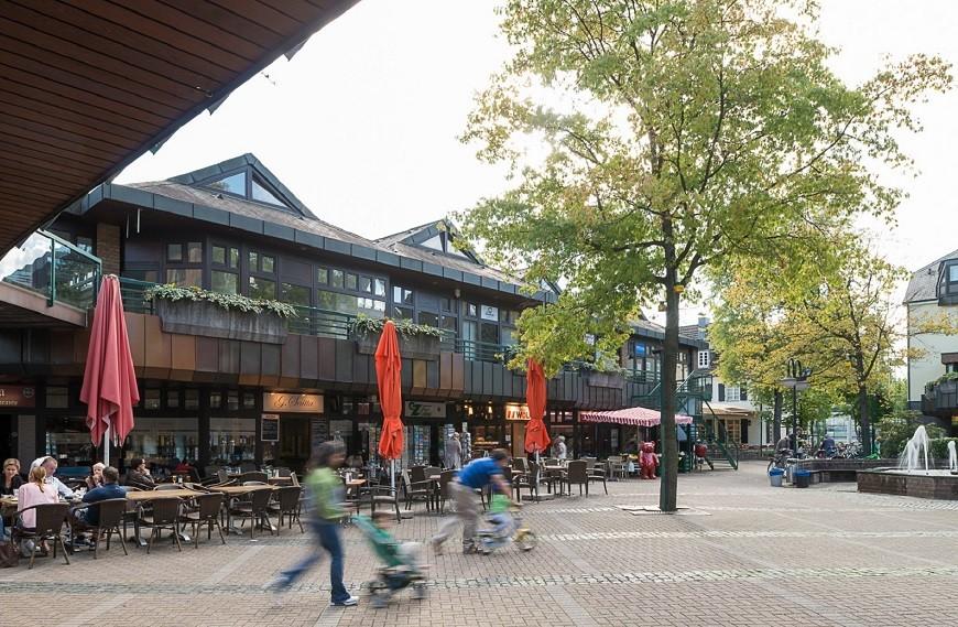 Klemensviertel Außenansicht belebter Brunnenplatz mit umliegenden Geschäften
