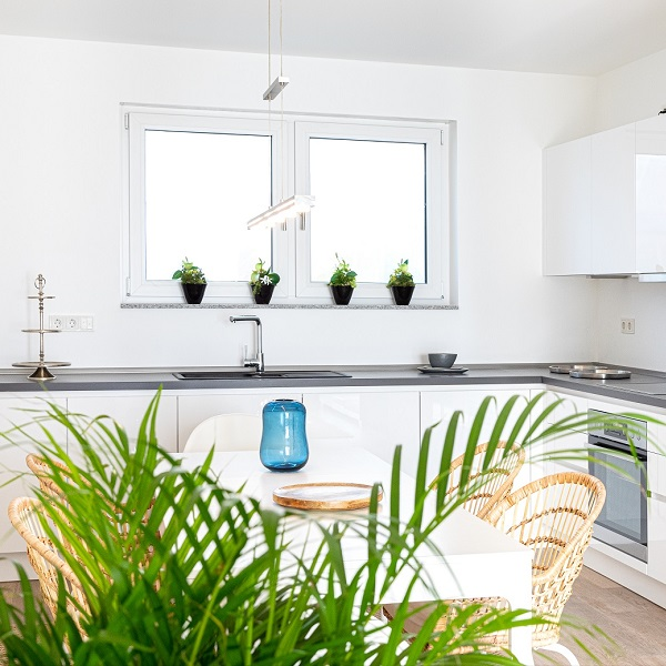 Arcadia Höfe sample apartment white kitchen with white dining table and wicker chairs