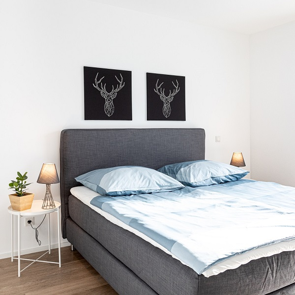 Arcadia Höfe sample apartment bedroom with dark blue box spring bed and light blue bedding