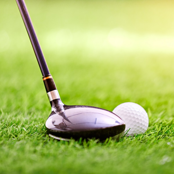 Golf club and ball on green gras